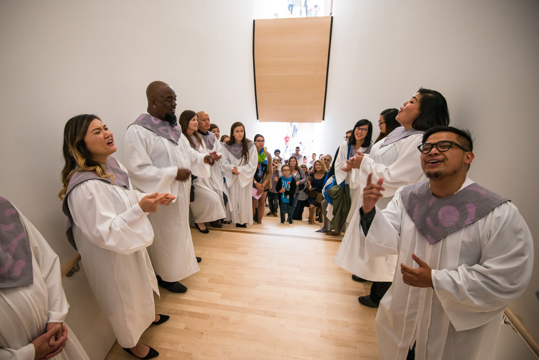 A group of people wearing white robes sing on a staircase, Paradise Choir, Kallmyer, Soundtracks