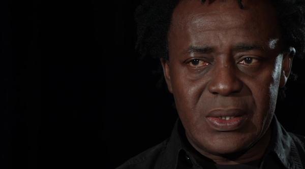 Screenshot of John Akomfrah speaking against a black background