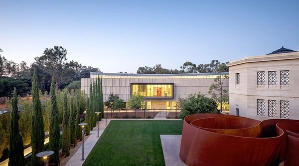 A manicured lawn leads past an iron sculpture toward a glowing museum