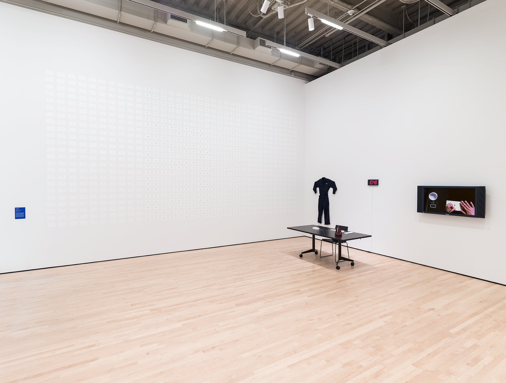 A gallery shows a grid of small white drawings, a jumpsuit, and a screen hanging on a wall before a desk, Munoz, Soundtrakcs