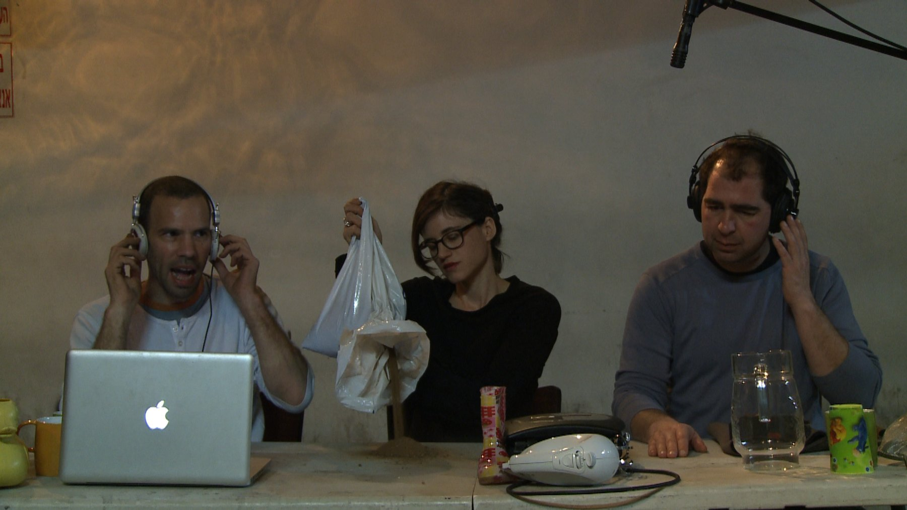 Two Caucasian men and one women sit at a table with a computer and various other items, Ben Ner Soundtracks