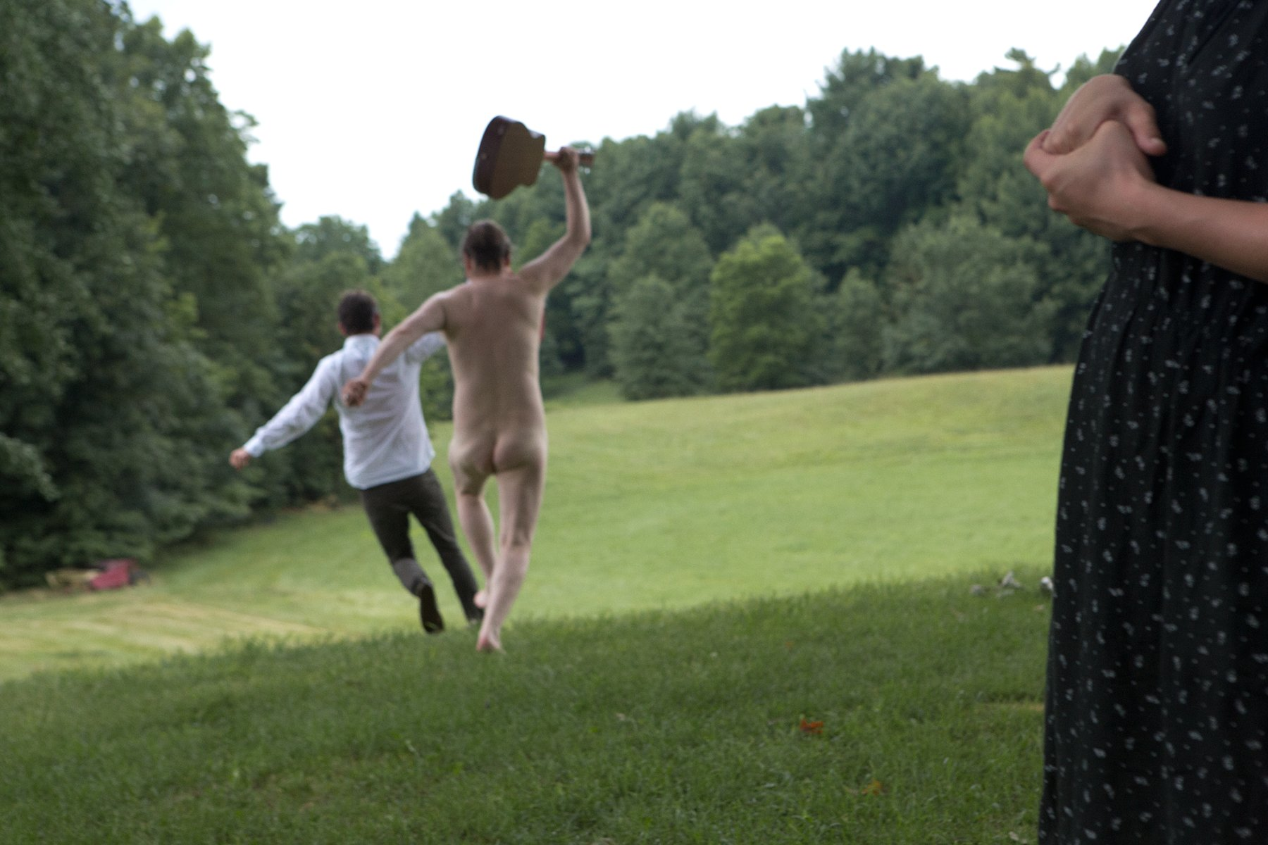 A naked Caucasian man holding a guitar chases another clothed man through a green field, Kjartansson
