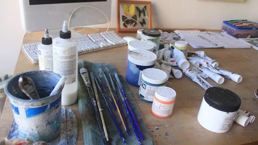 A desk featuring artist materials, such as paint brushes, jars of paint, a computer keyboard, Travis Collinson