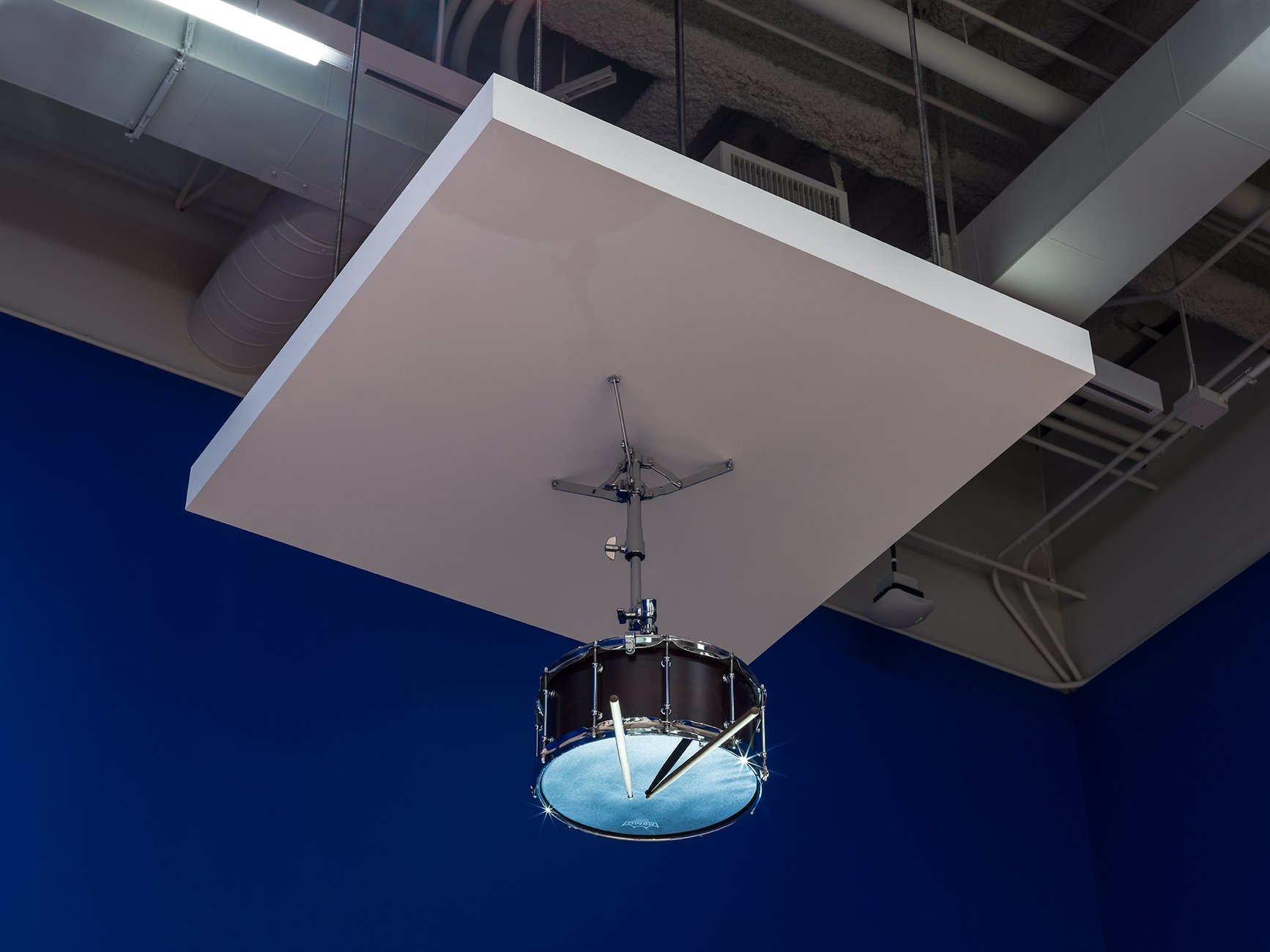 A snare drum hangs from the ceiling before a royal blue wall, Sala, Soundtracks