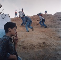 Yto Barrada, men climbing rock crossing border with young boy in foreground