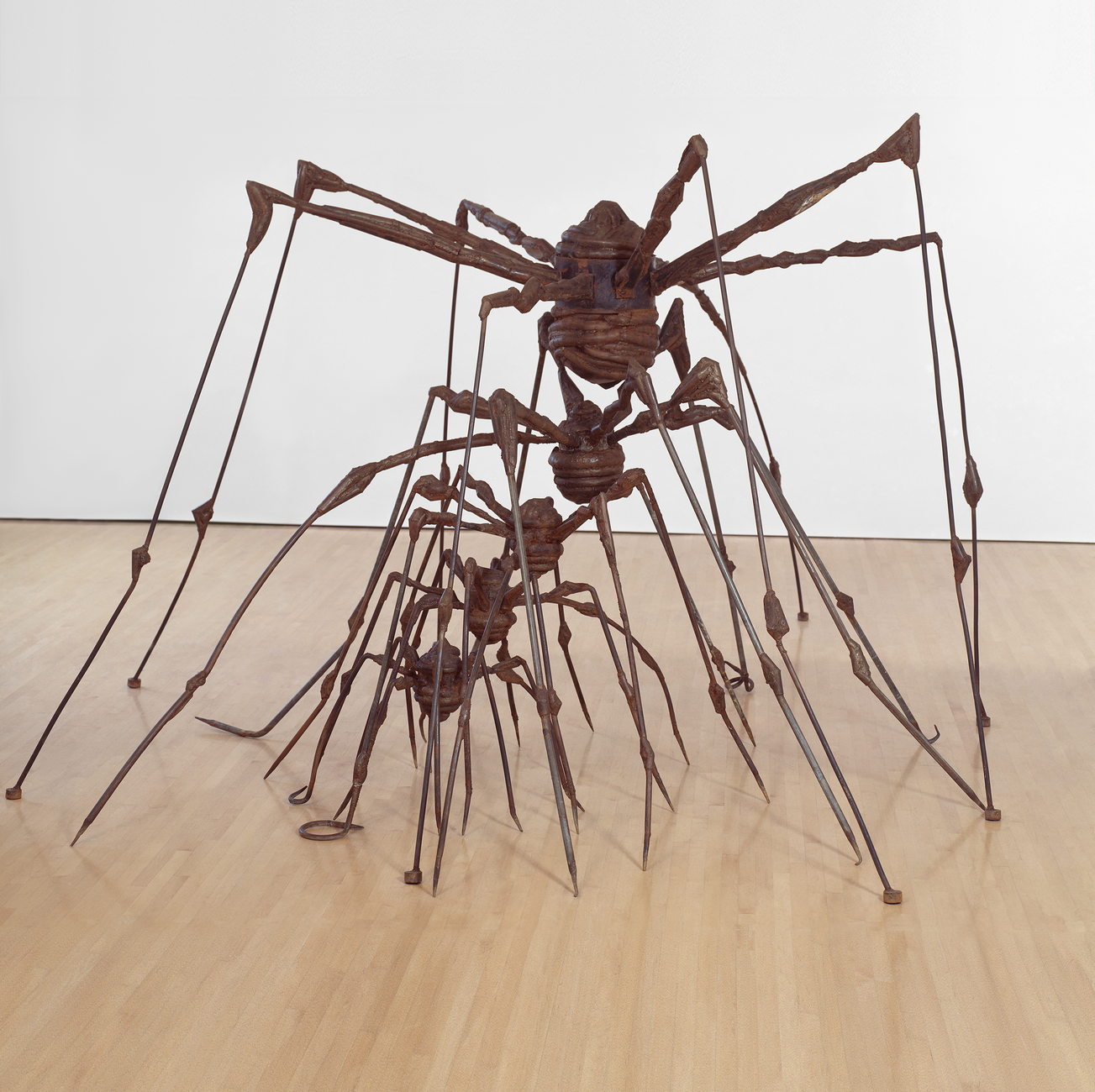 A large metal sculpture of a spider with smaller metal spider sculptures nested between its legs