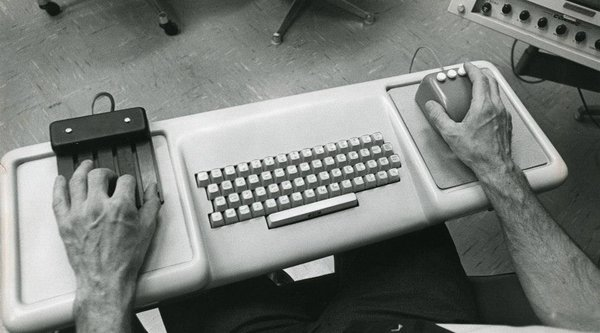 Two disembodied arms set on a white keyboard holding two old computer mice; Typeface to Interface