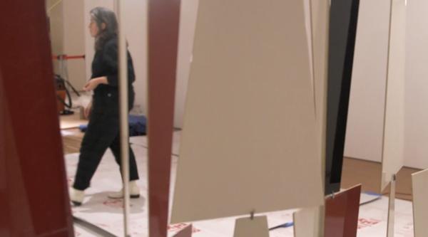 Artist Leonor Antunes installing an artwork