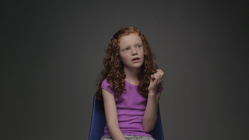 young girl in purple sitting on chair gazing to side