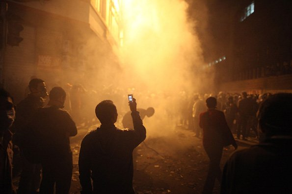 Protestors in a smokey street film on cell phones