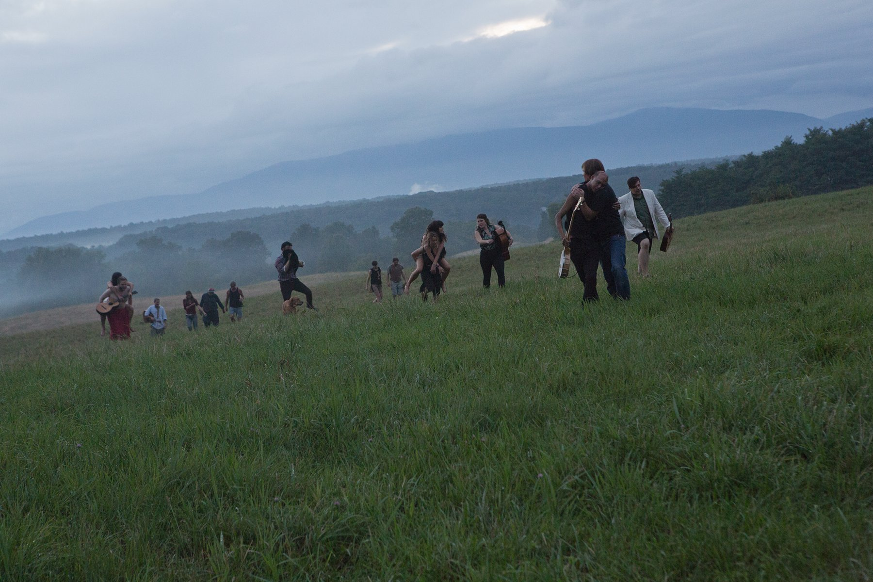 Several people stand in an open green field at dusk, Kjartansson