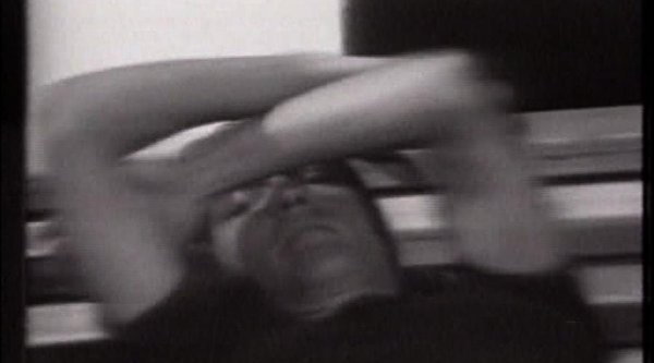 Grainy black and white photo of a man with his arms crossed over his face