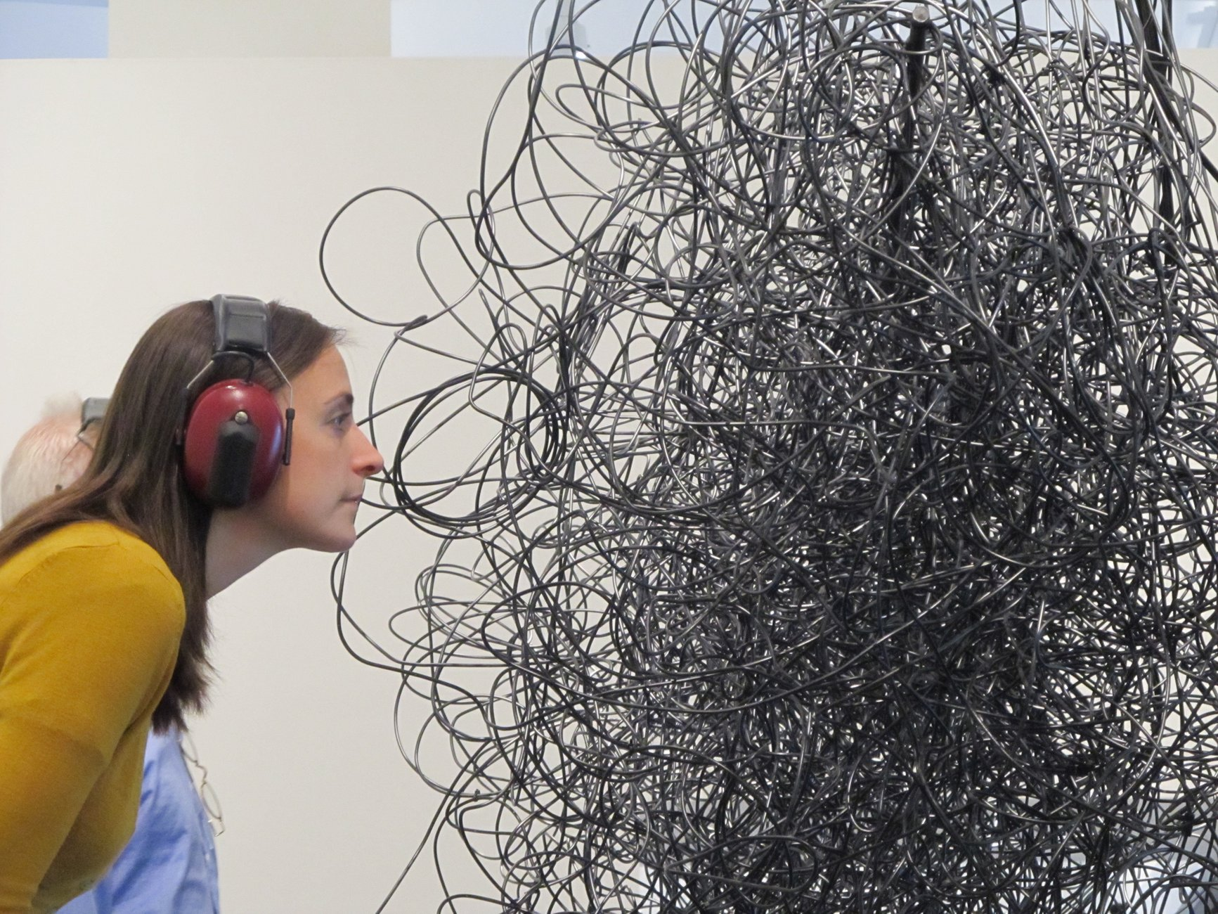 A Caucasian woman wearing read headphones leans into a sculpture in the form of tangled wires