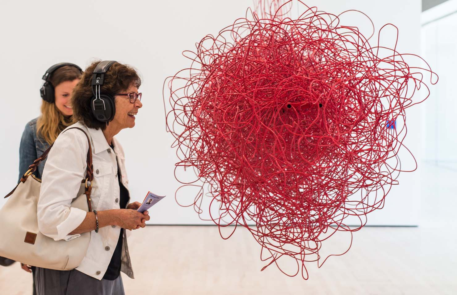 A middle-aged Caucasian woman wearing headphones smiles before a cloud made out of red electrical wires, Kubisch, Soundtracks