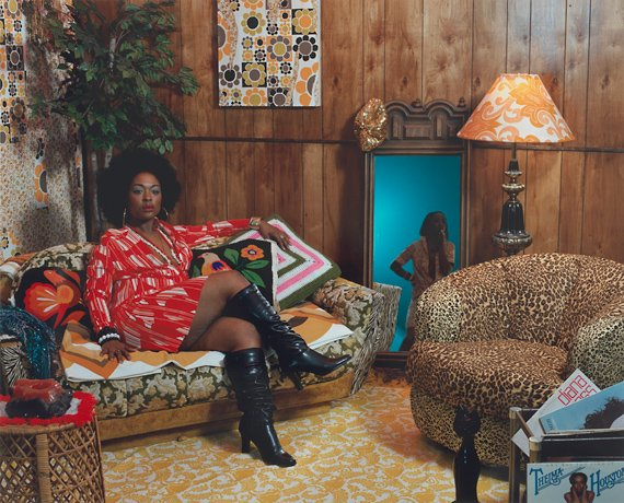 Mickalene Thomas, woman in red dress sitting on couch in colorful living room