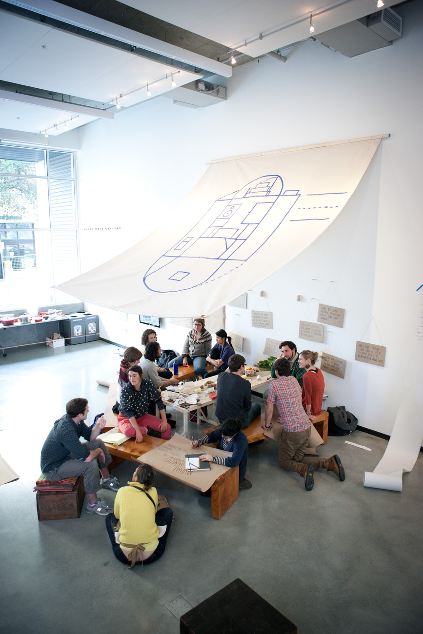 A group of young adults sit around an indoor picnic table with an canvas srchitectural floorplan hanging over them