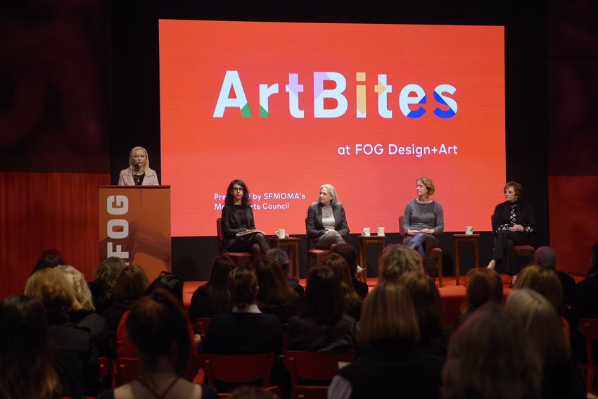 Five women sit on a stage before a large red screen with the words ArtBites