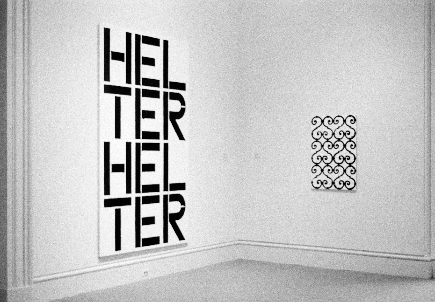 "A large black and white painting that reads ""HELTER HELTER"" next to a black and white painting of a fence-like pattern"