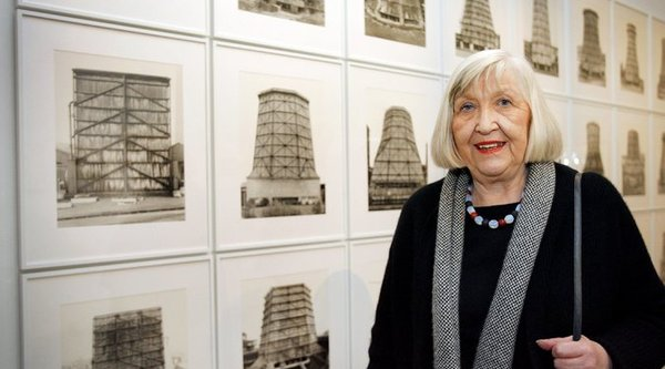 An elderly woman with white hair stands before a grid of black and white photographs