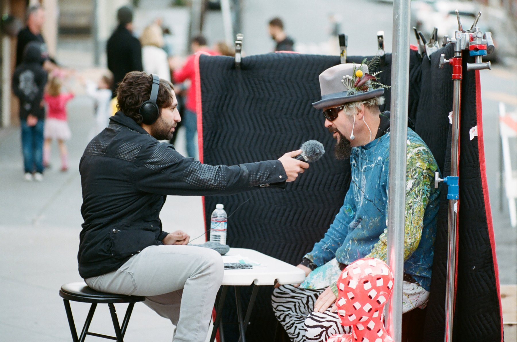 a person dressed in eccentric prints is interviewed on a sidewalk