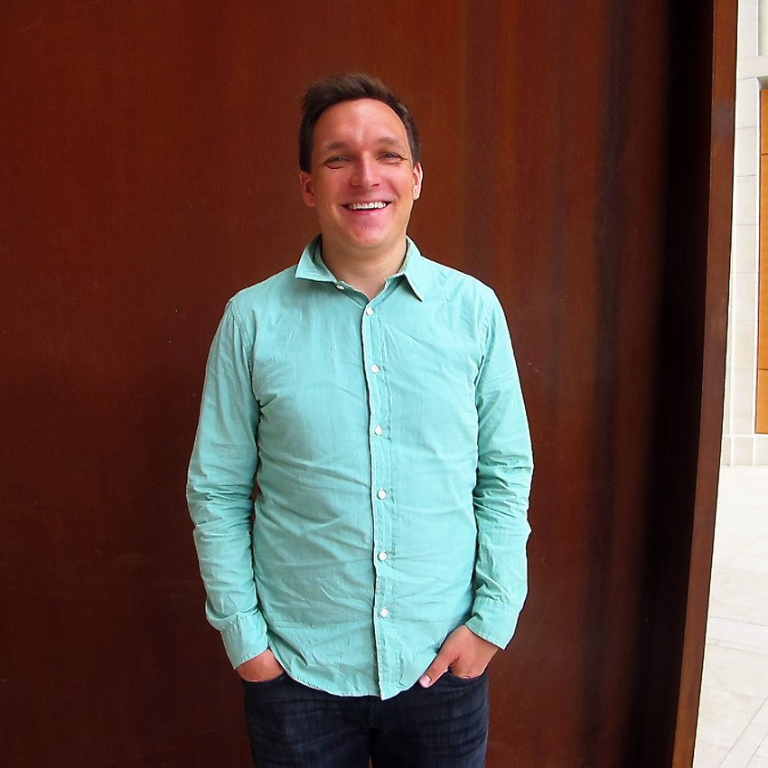 A man wearing a turquoise sweater stands smiling