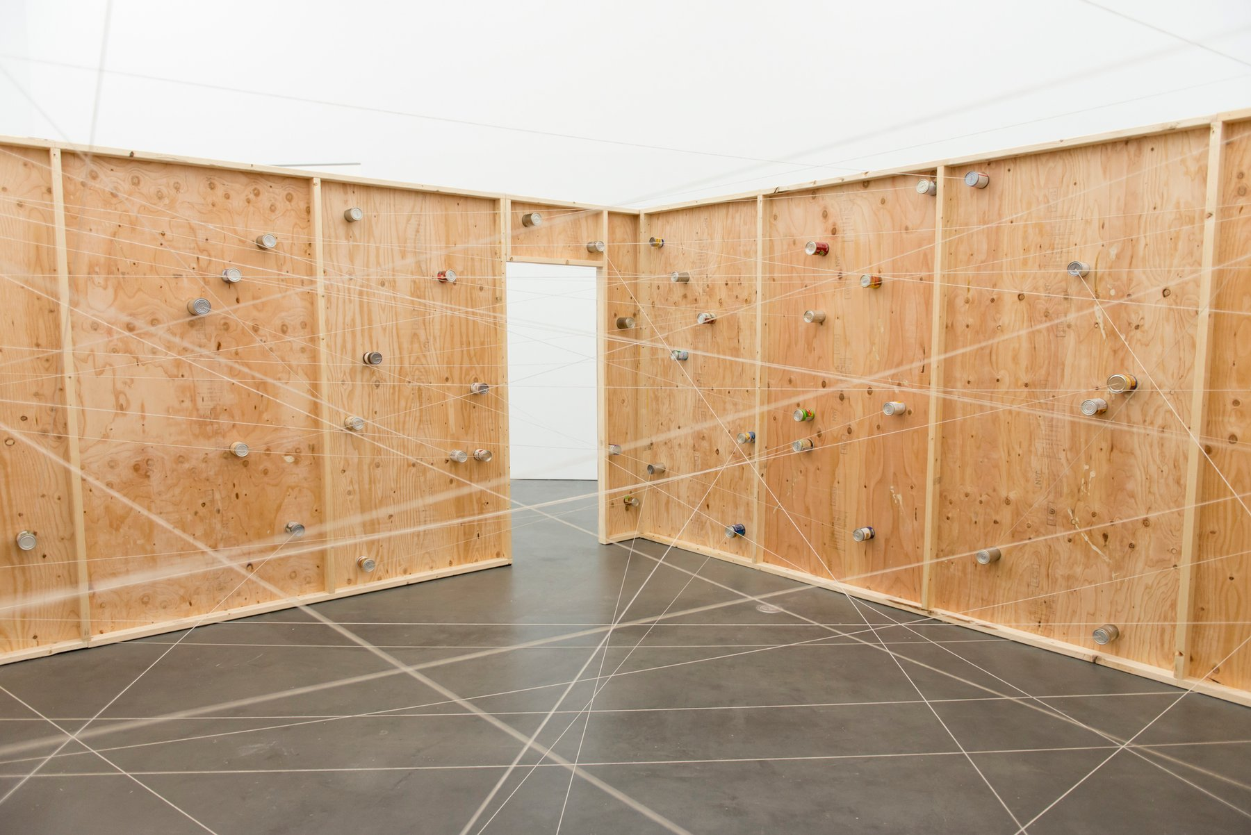 A wooden structure with a doorway into an empty white gallery, Pica Soundtracks