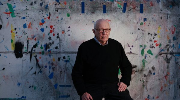 An elderly man wearing glasses sits before a painted canvas