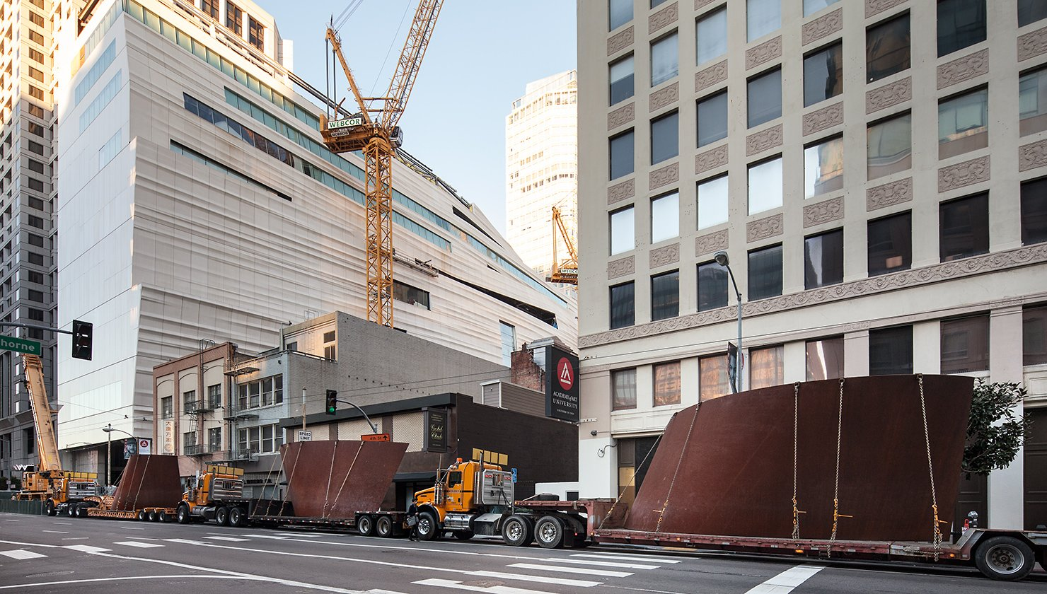Large bronze sculptural coils are transported along a city street