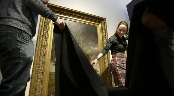 Artworks being covered in a black shroud