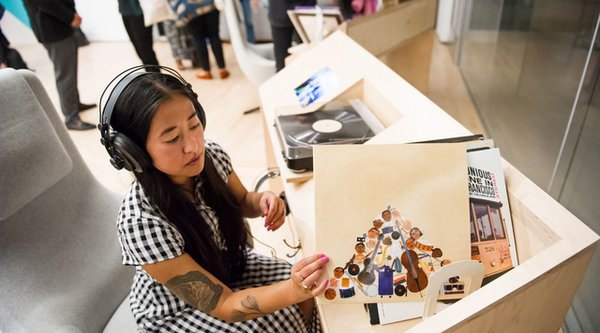 An Asian woman wears headphones and looks at ephemera, Public Knowledge