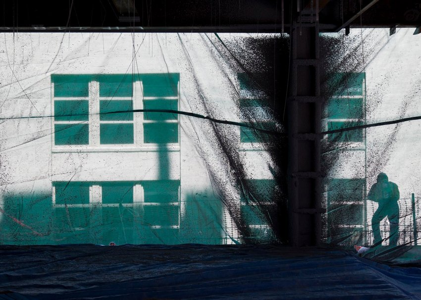 Workers cast shadows against a protective mesh on a floor under construction