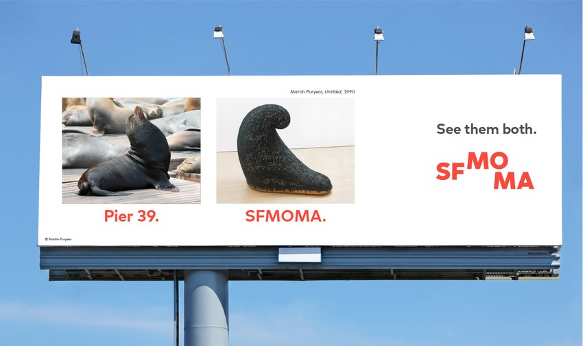 An advertisement with a seal at Pier 39 next to a Martin Puryear sculpture