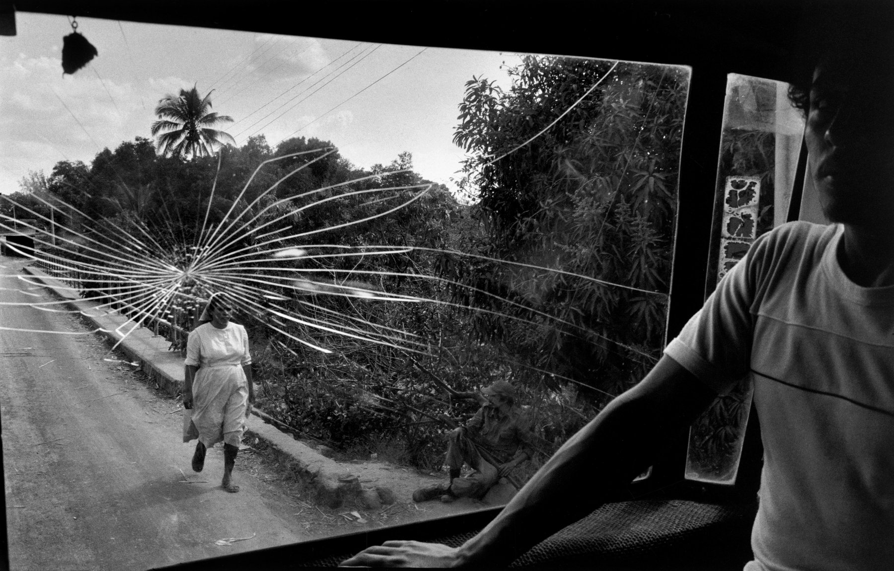 A man standing near the cracked window of a bus, which looks out onto a rural road where a woman in a white headscarf walks and a soldiers sits watching her