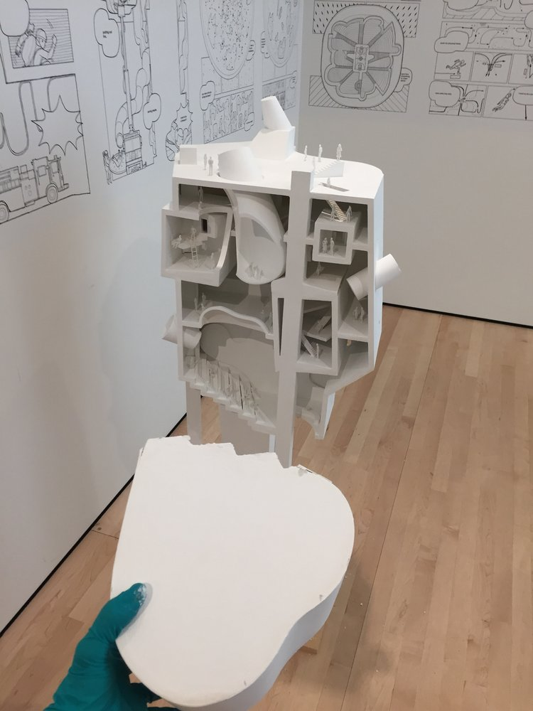 A gloved hand holds a white piece of foam core against an architectural model, Jimenez Lai