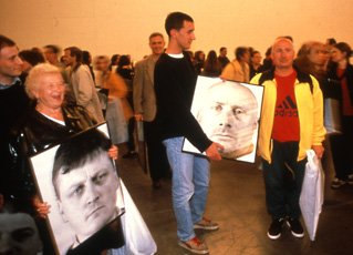 Gerz, crowded room with two people holding images of men's portraits