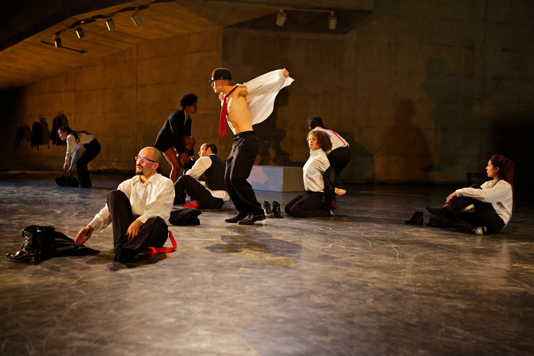 Figures wearing white shirts, red ties, and hats perform on a flat stage, Anna Halpern Soundtracks