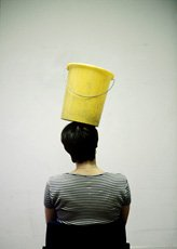 Erwin Wurm, photo of back of person balancing yellow bucket on head