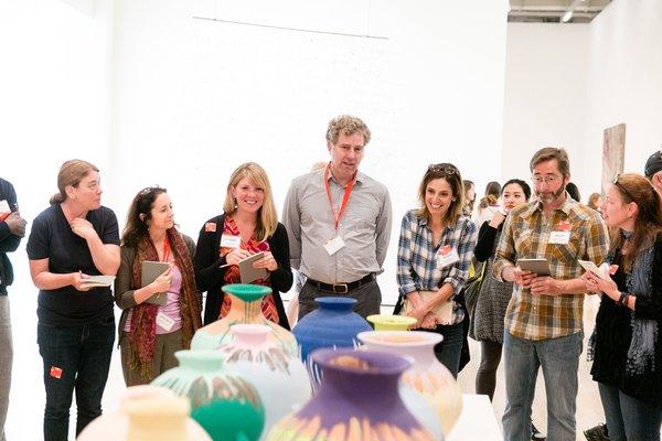 A group of teachers study an artwork