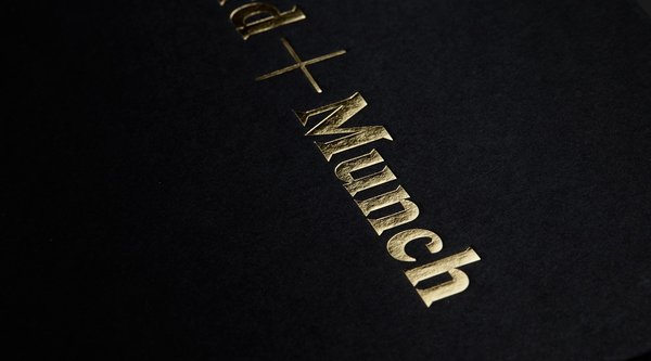 A black top with the words + Munch embossed in gold