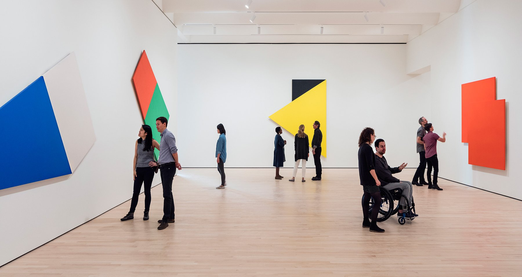 A group of people looking at paintings by Ellsworth Kelly