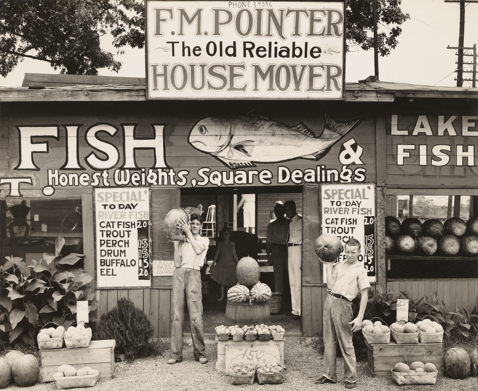 "Two boys holding watermelons stand outside of a stand with a rooftop sign reading ""F.M. Pointer - The Old Reliabe - House Mover"" and the front wall painted with a fish and the words ""FISH: Honest Weights, Square Dealings"""
