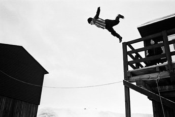 black and white photo man jumping off building onto tight rope