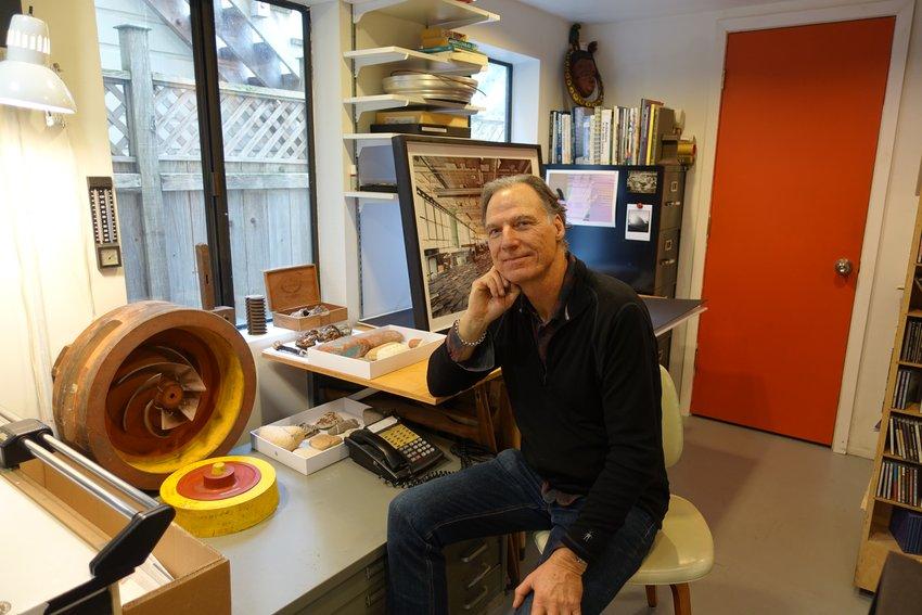 Photographer Henrik Kam sits at a desk in his studio