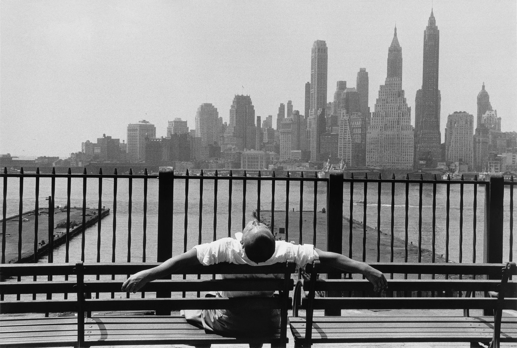 A man sitting on a bench with both of his arms behind it in front of manhattan skyline