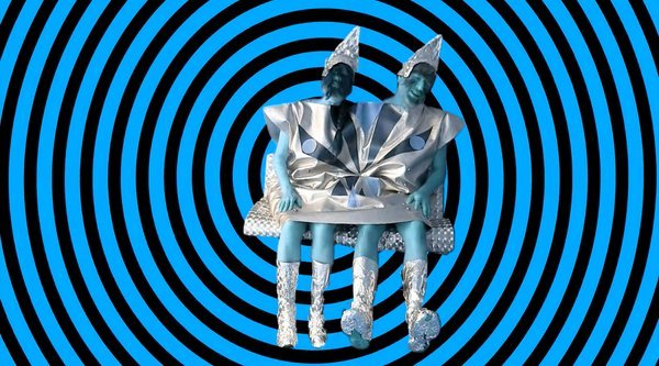 A blue and black striped background with costumed performers wearing silver hats, Gallardo