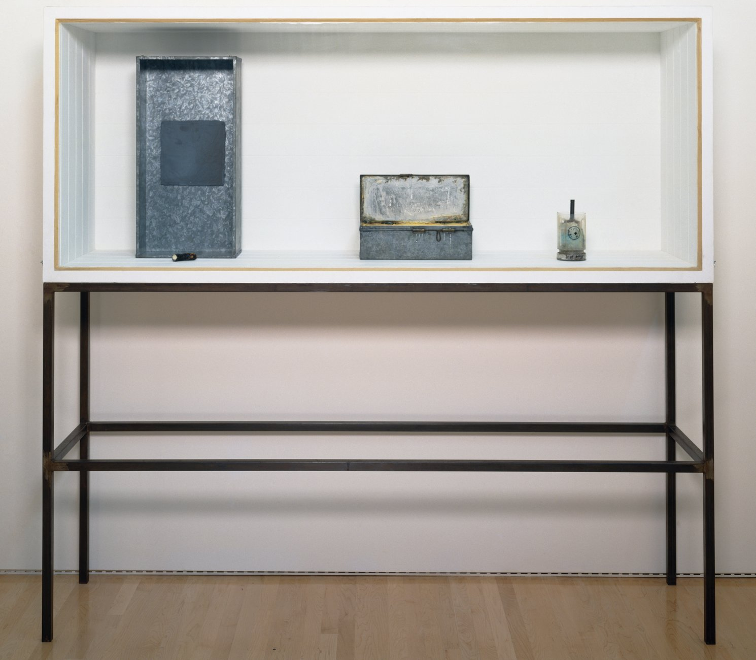 A white-walled vitrine atop thin steel legs, containing several metal and glass objects