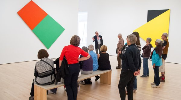 A museum guide soeaks to a group in front of an Ellsworth Kelly painting