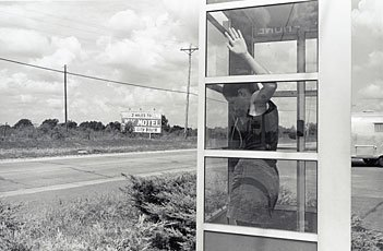 Wessel, woman in telephone booth on side of road in Oklahoma