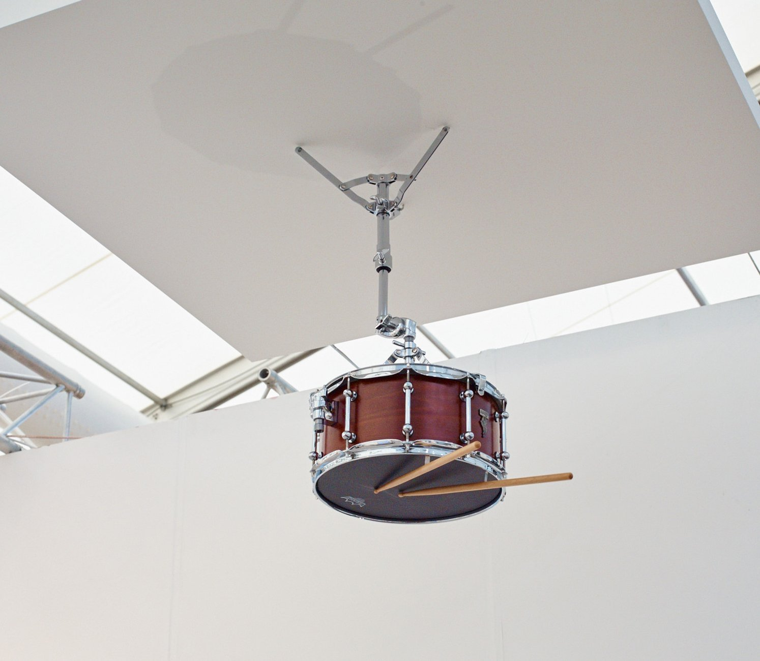 A single snare drum and two drumsticks are suspended from a ceiling panel