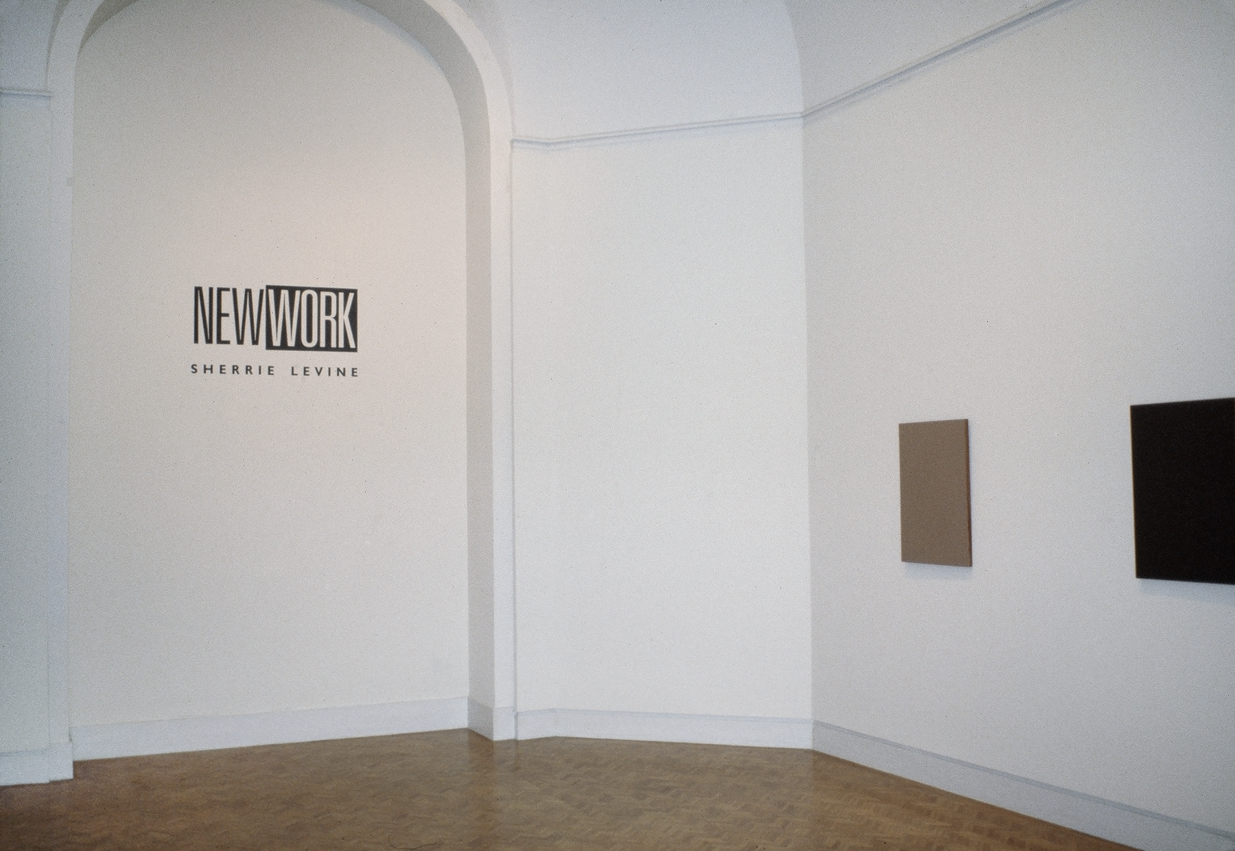 "One brown and one black canvas hanging in  a gallery with the words ""New Work: Sherrie Levine"" on the wall"